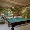 The billiards room Has murals On The wall that exude An outdoor ambiance